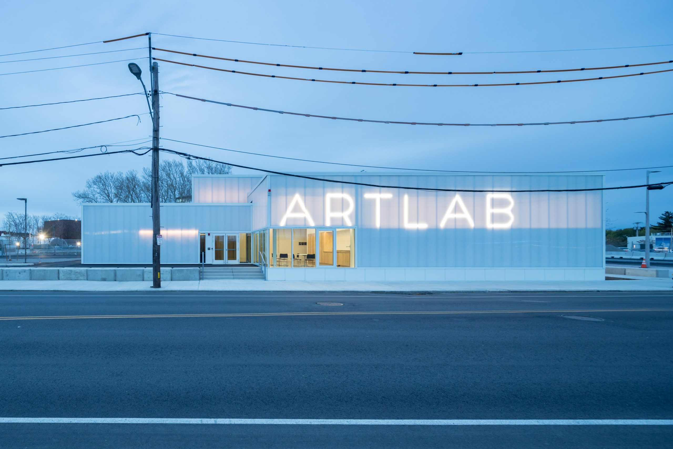 A white building with large lit letters reading ARTLAB.