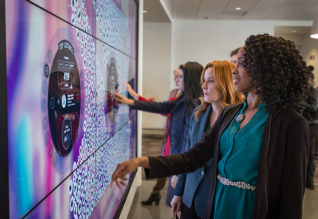 People point at a large touch screen.