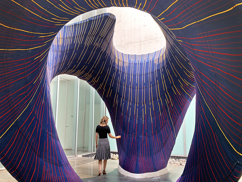 A person walk through an undulating patterned pavilion