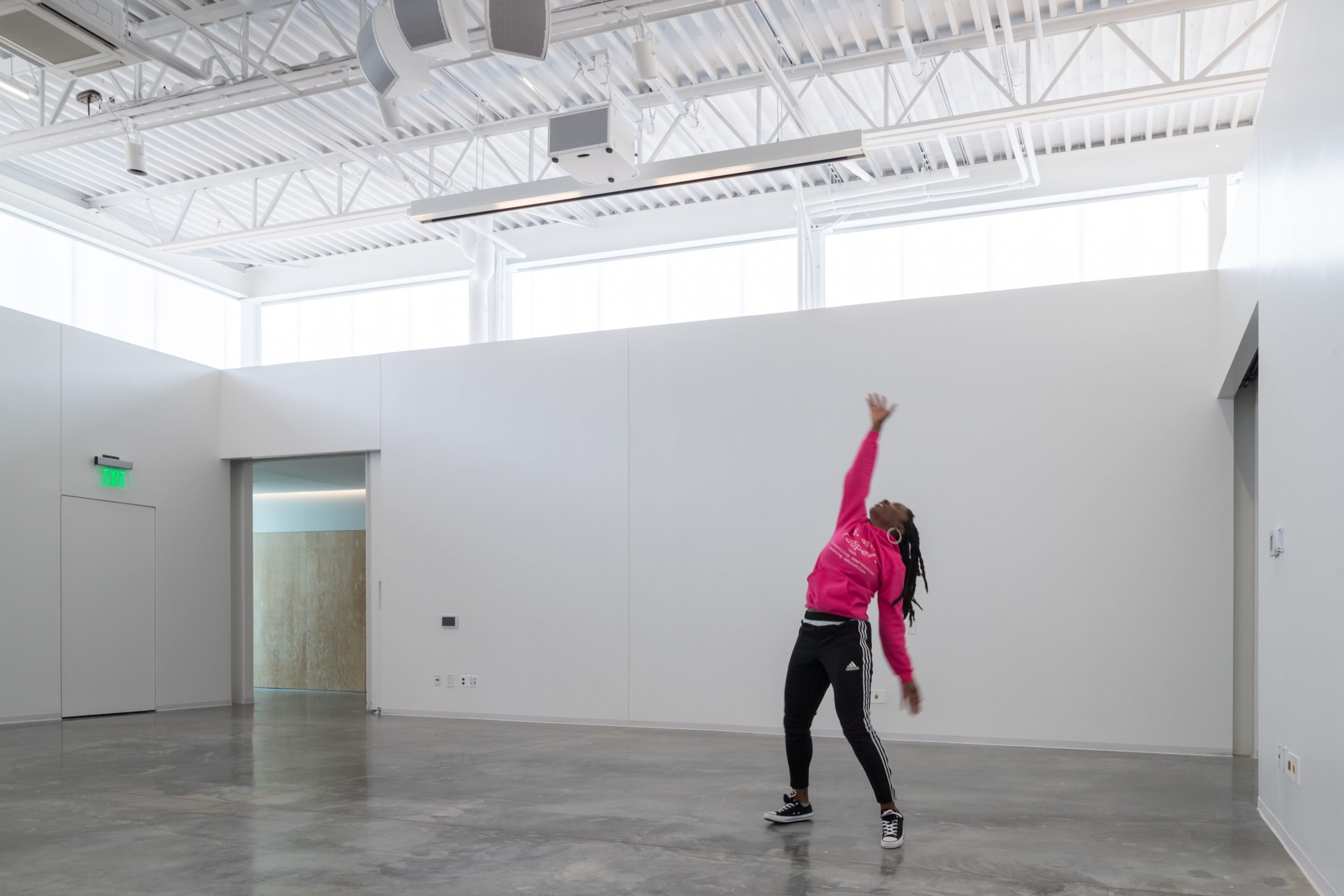 Interior photo of a woman dancing inside of a bare studio in the ArtLab