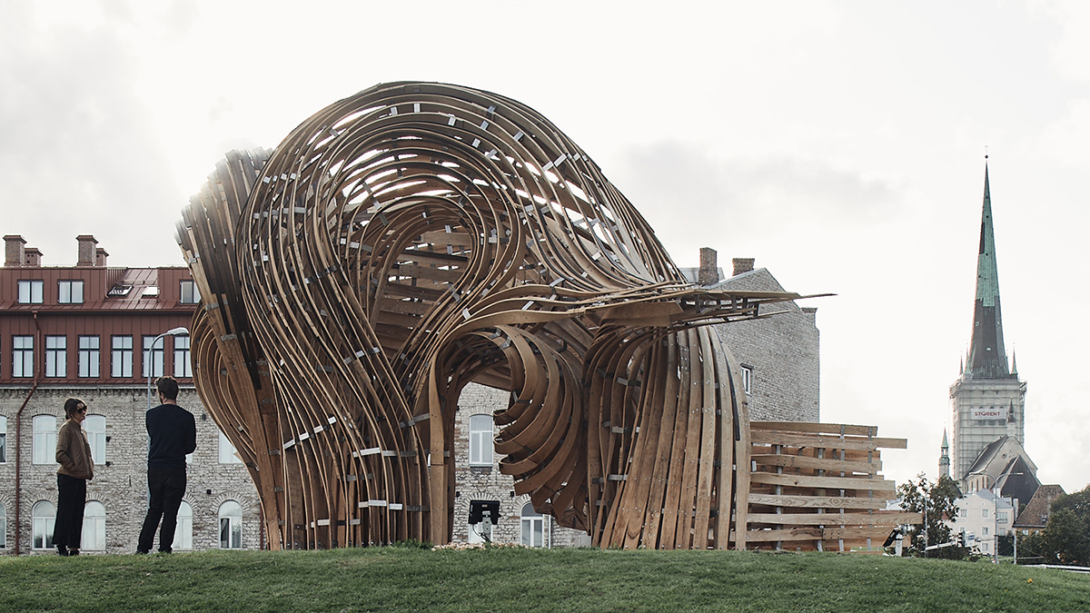 A large curbed wooden structure made of interwoven planks.
