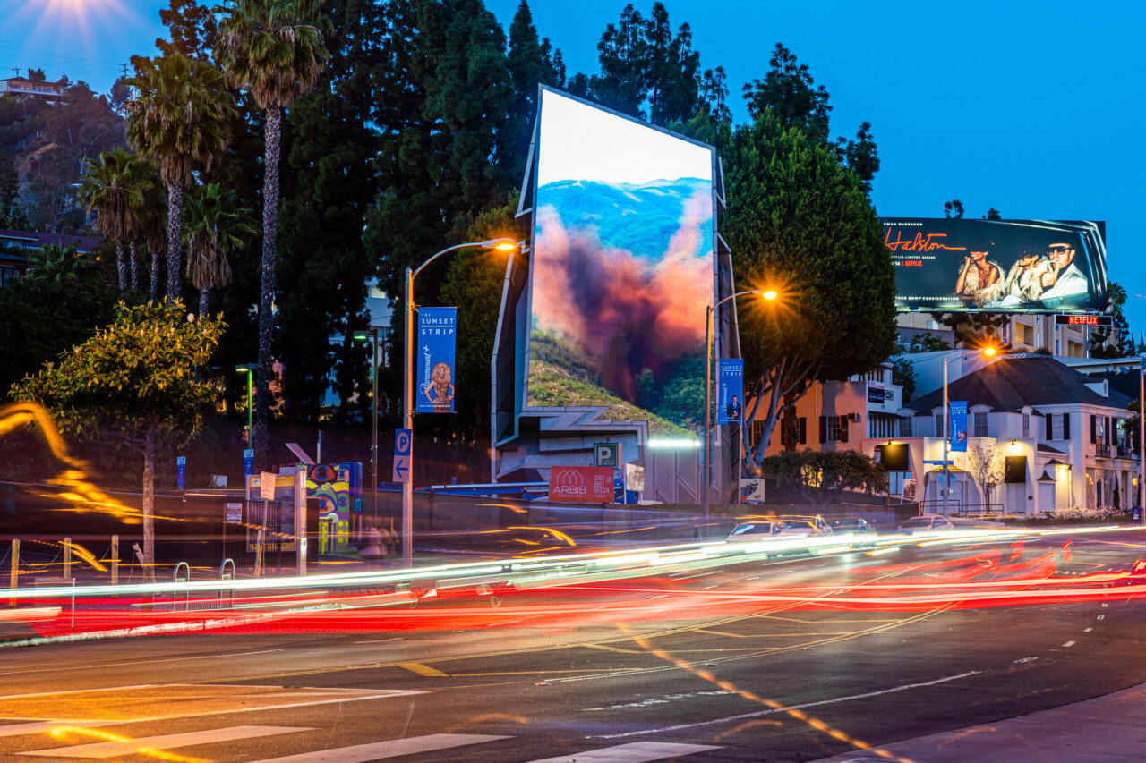 artwork of an explosion in a forest scene on the LED billboard of wiscombe's sunset spectacular