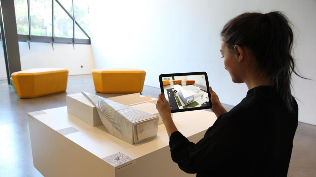 A person using an iPad to view AR effects over a model of the BAMPFA.