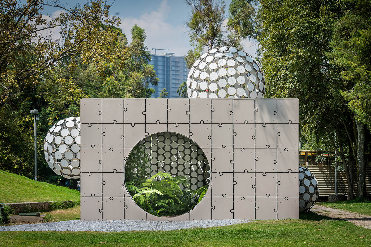 A concrete cube pavilion with puzzle piece–like panels that has bulbous forms made of white circles growing out of it.
