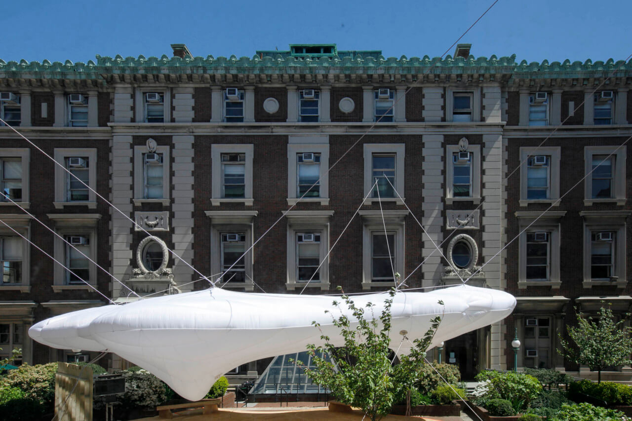 an inflatable pavilion anchored between three neoclassical red brick buildings