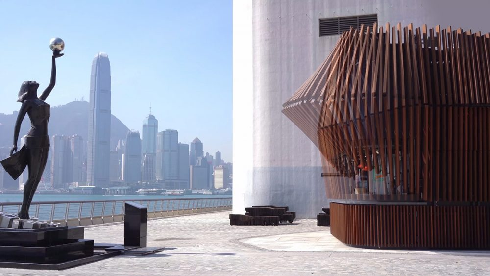 An image of a timber-finned kiosk on the harbor front with skyscrapers visible in the background and a statue visible in front. Overlayed on the picture is the wooden fins both open and closed.