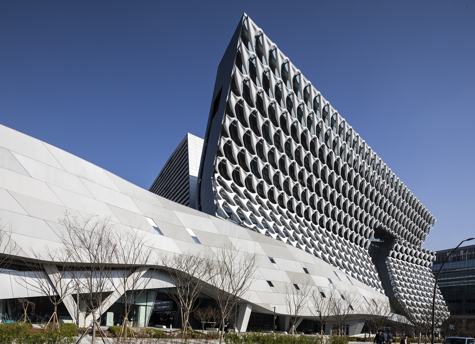 A tall building with a sweepiing facade made of interlocking white Ts, designed by Morphosis. The building continues at a lower height as a undulating gray roof with some irregular fenestration.
