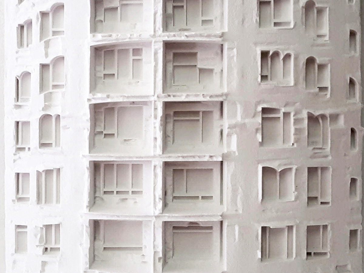 A white model of an irregularly fenestrated facade
