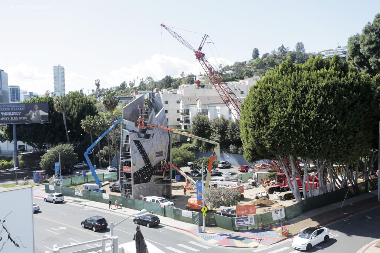 image of construction site of the new structure. Image includes a crane, cars, and trees at sunset spectacular