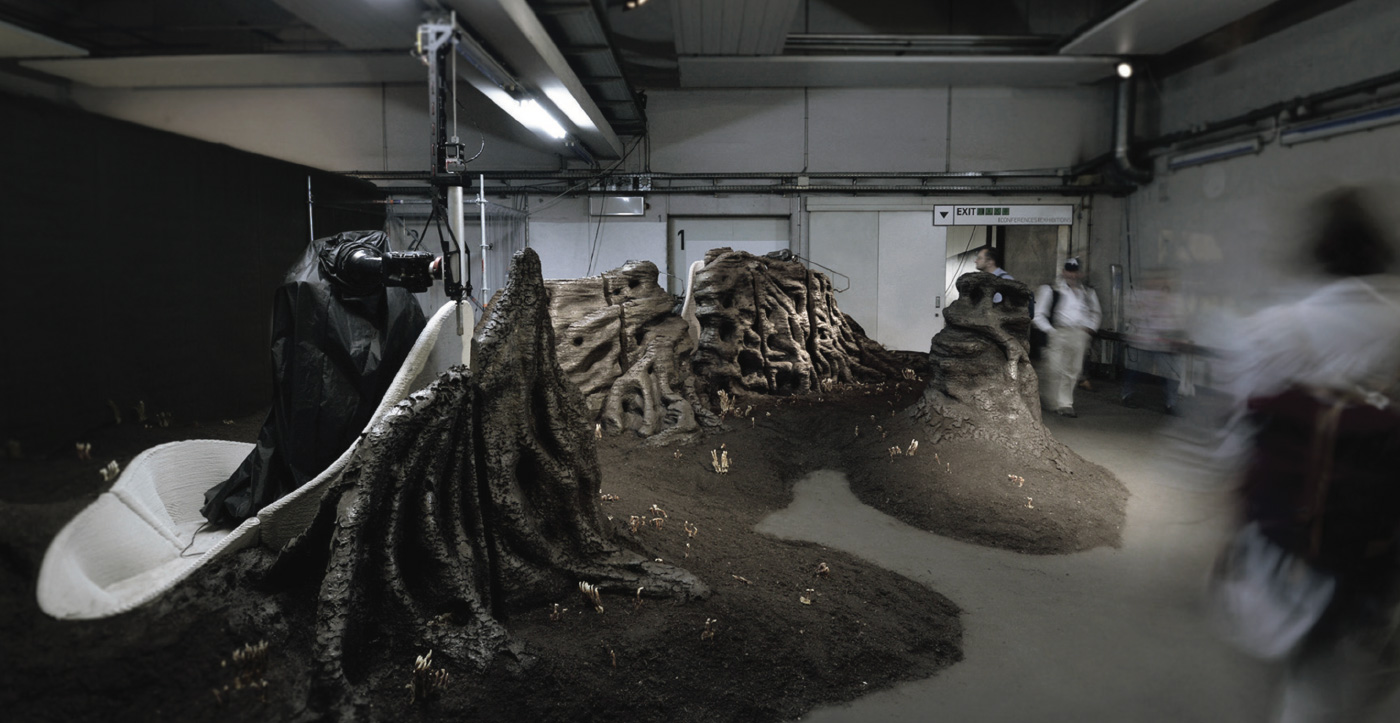 A cellar-like room is filled with printed piles of soil.