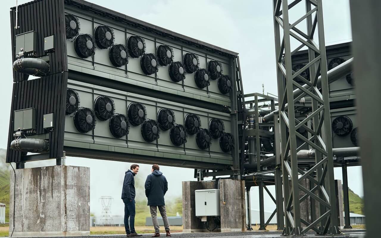 Outdoor landscape and several fans attached to large box at a carbon capture facility