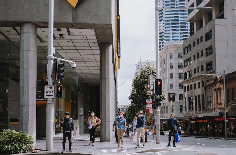 pedestrians wait to cross an empty city street, part of a street closures program