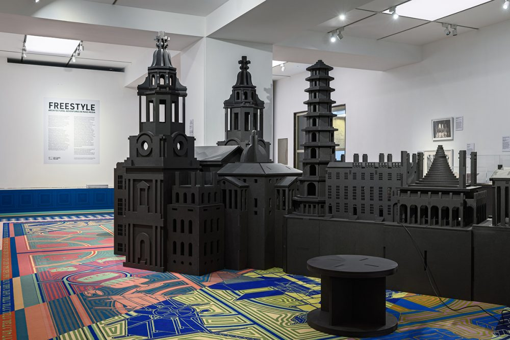 A large black architectural model on a colorful carpet