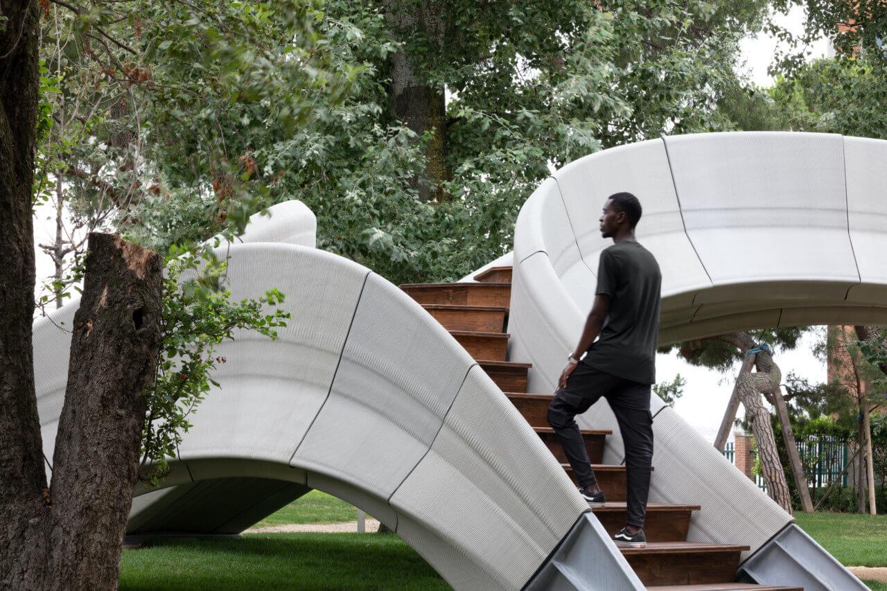 a man walking up stairs onto a concrete footbridge bridge, striatus