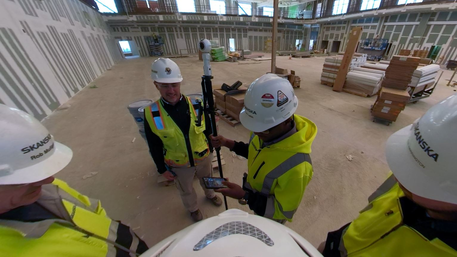 Photo of construction workers standing around a monopod with a camera