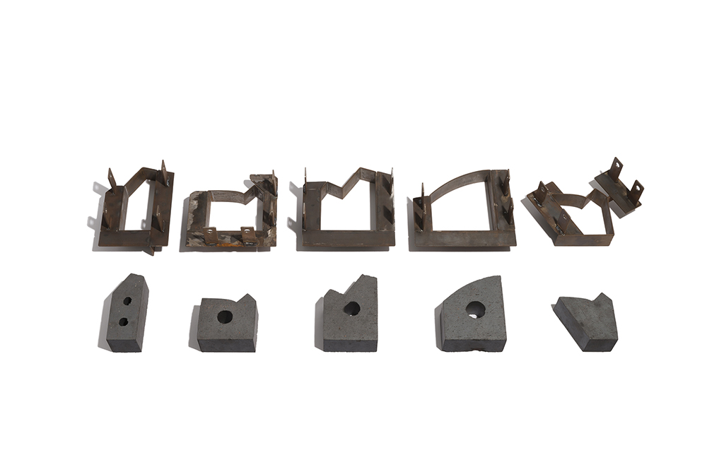 A photo of a selection of non-traditionally shaped bricks and the steel molds used to make them