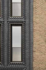 Photo of two facades side-by-side—one traditional brick, the other multiply-oriented gray brick