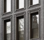 Close-up photo of a facade of interlocking blue-gray bricks that appear to be rotating in and out of each other