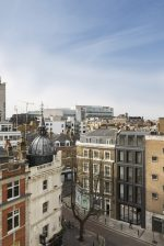 An aerial photo of a London street corner with the gray brick building by Bureau de Change in view.