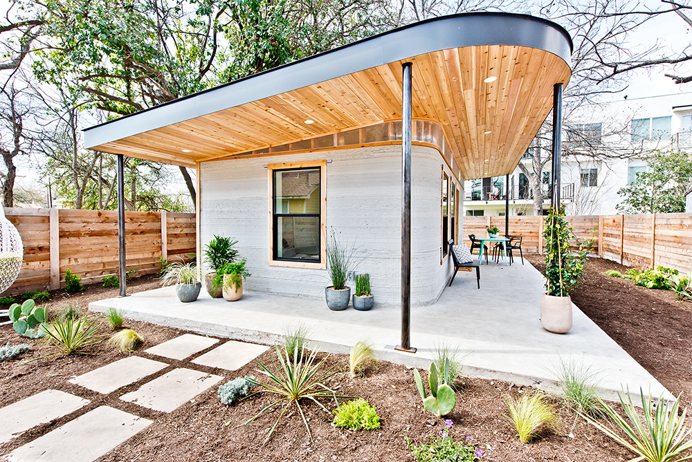 Photo of a small 3D-printed home with a large overhanging wooden roof