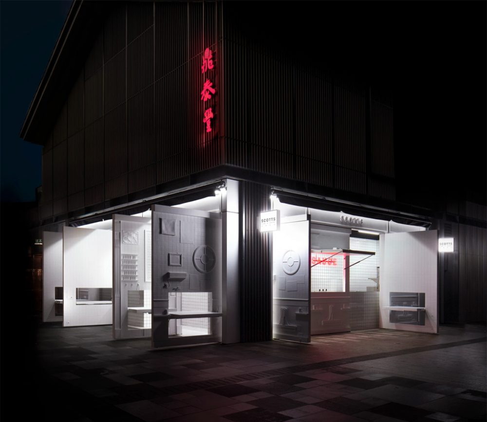 A night shot of a white fish and chips restaurant with doors opened to the street.
