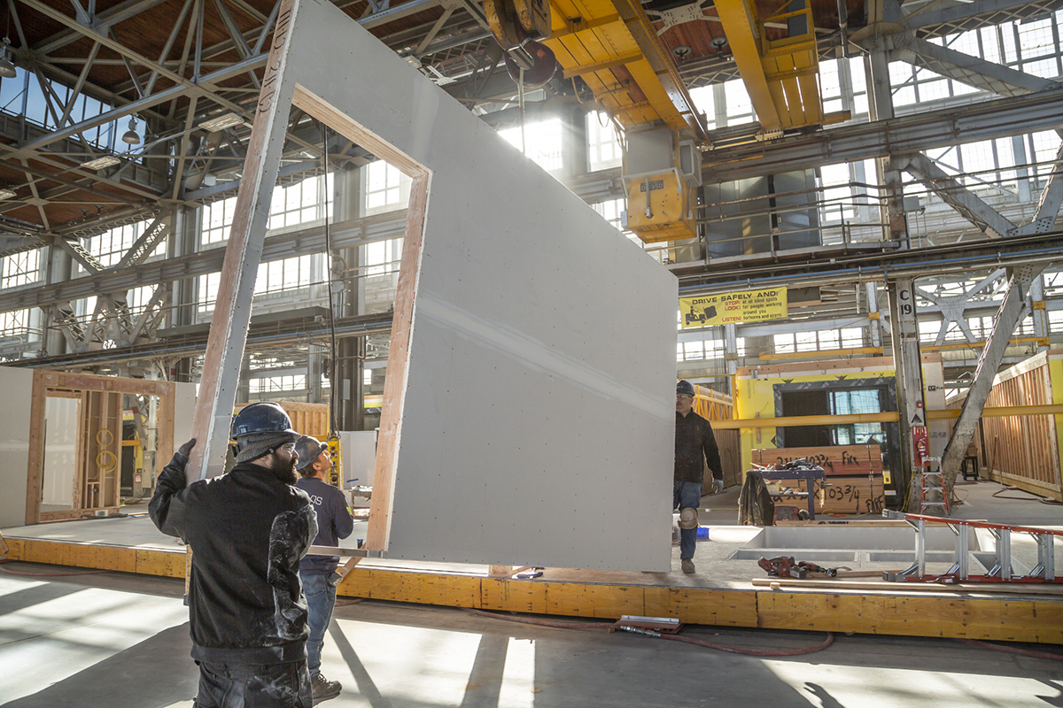 Workers carry a large segment of wall in a prefab housing factoring with a doorway cut out on a factory floor.