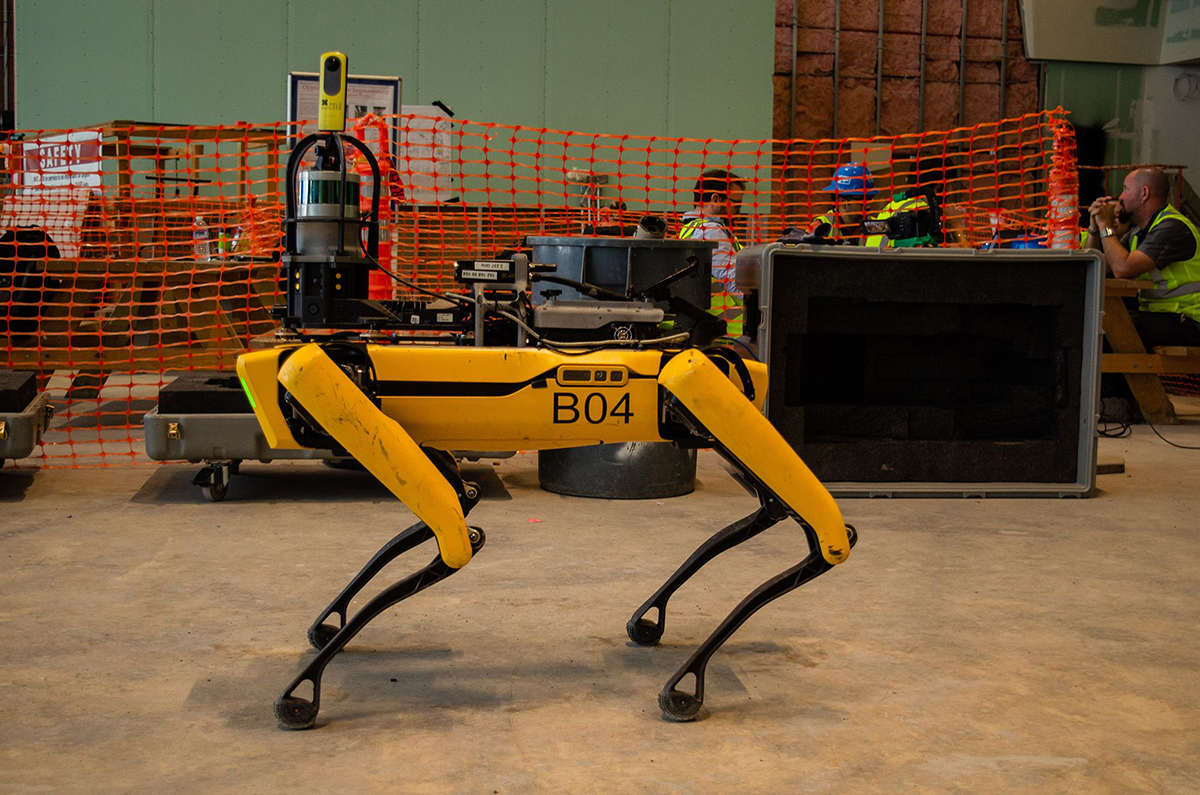 A yellow four-legged robot dog on a construction site, one of the Spot models from Boston Dynamics