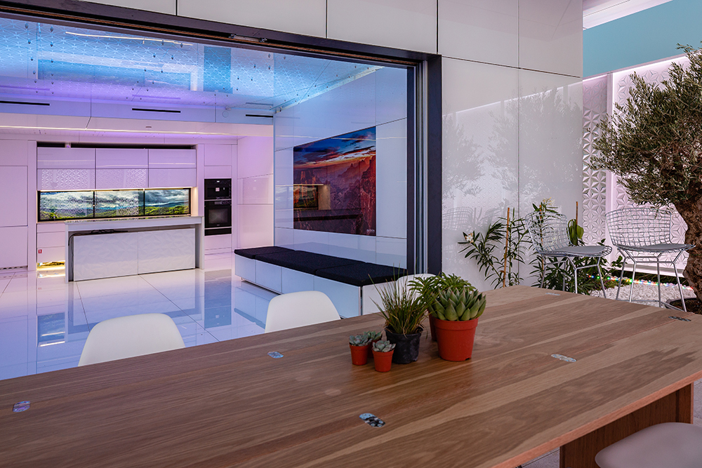 Rendering of a table with succulents in the foreground of a sleek white interior with purple and blue lighting