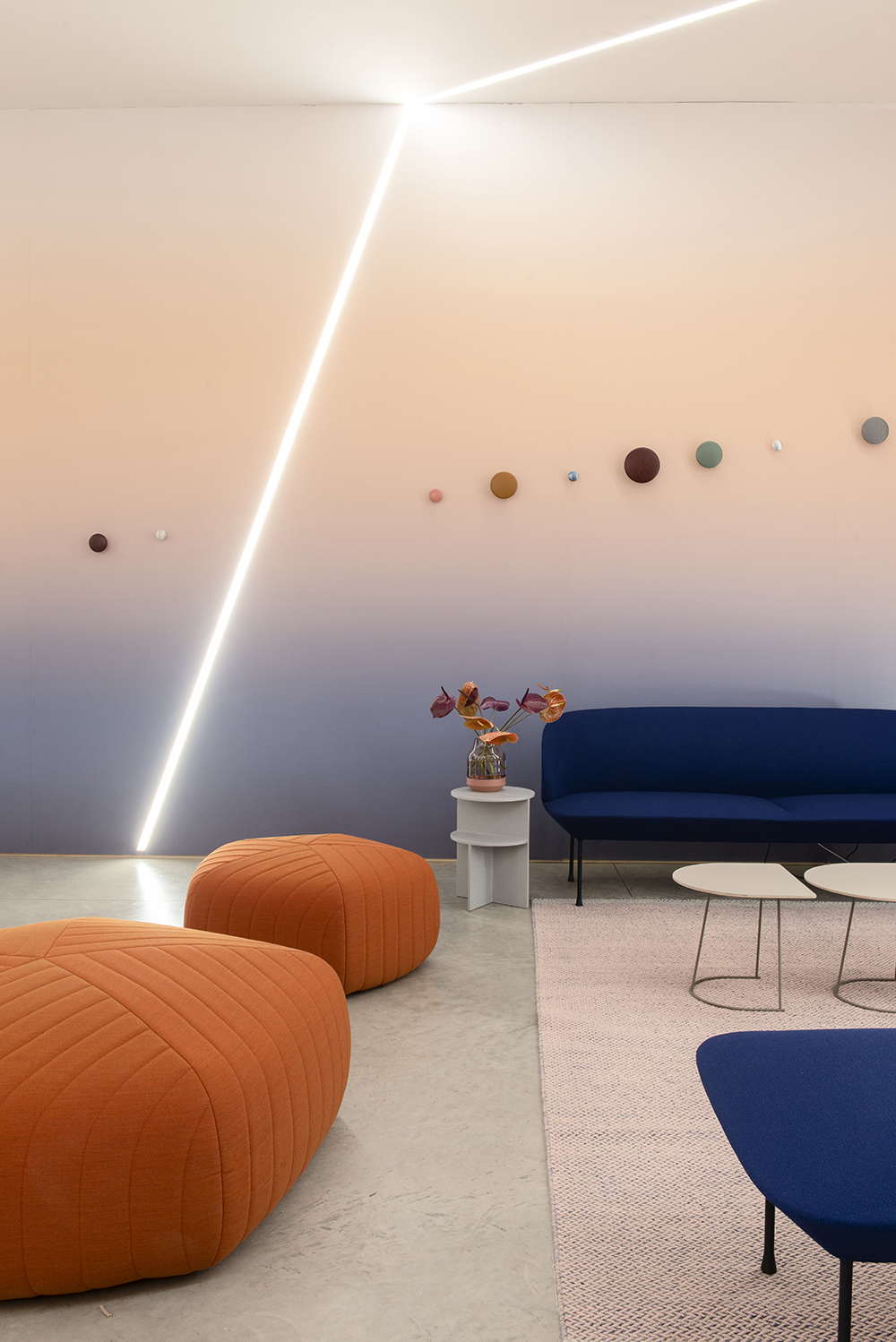 Photo of a room with a blue to peach gradient wall and orange and blue seating