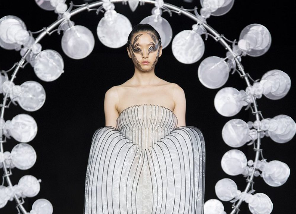 A model in a structured, widening dress comprising slits of fabric walks through a ring of rotating silk leaves designed by Iris van Herpen