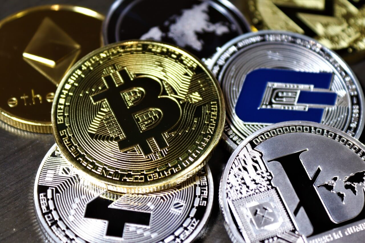 A pile of bitcoins on a table amid other cryptocurrency, which is currently being mined by greenidge generation