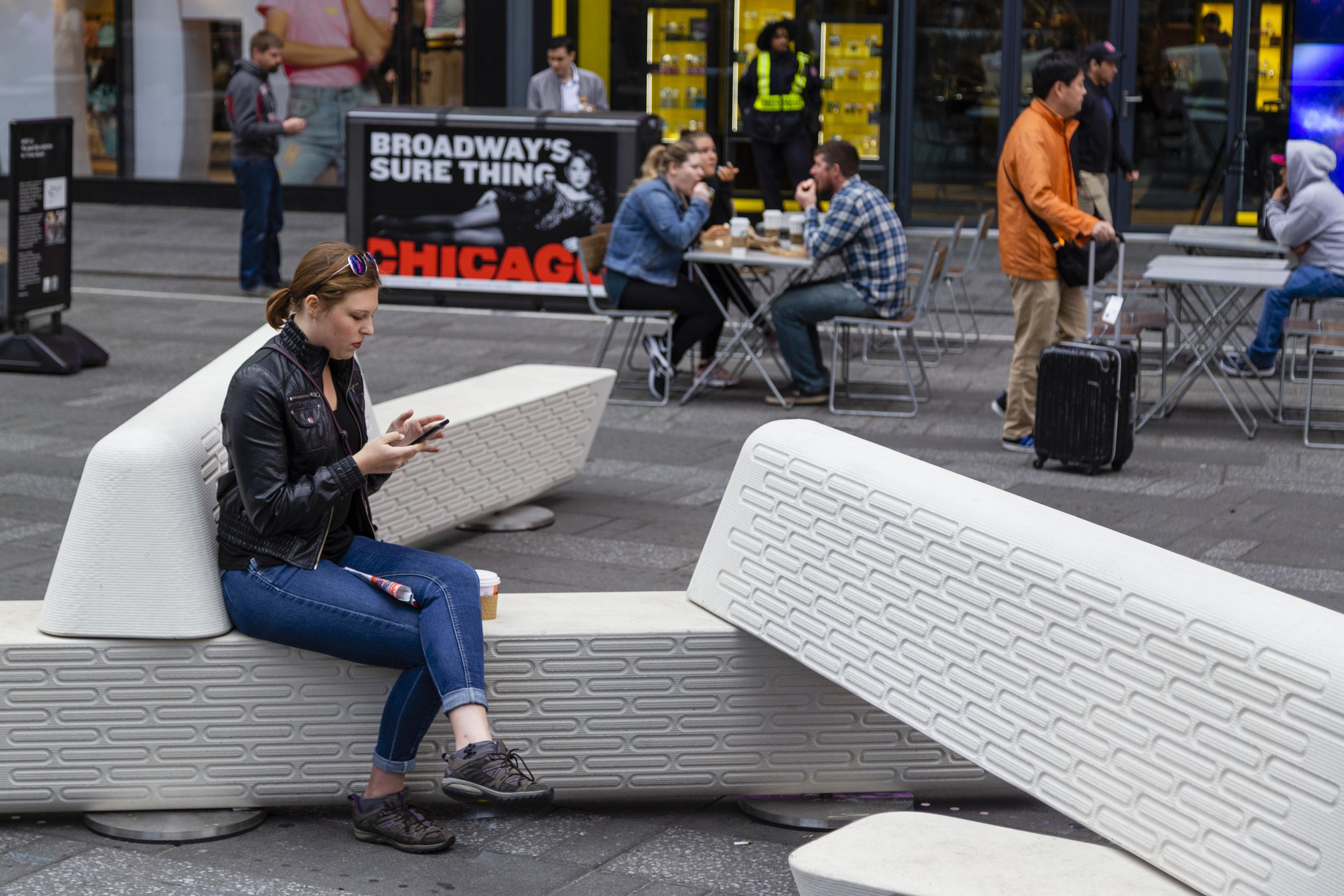A person sits on interlocking benches in Times Square.