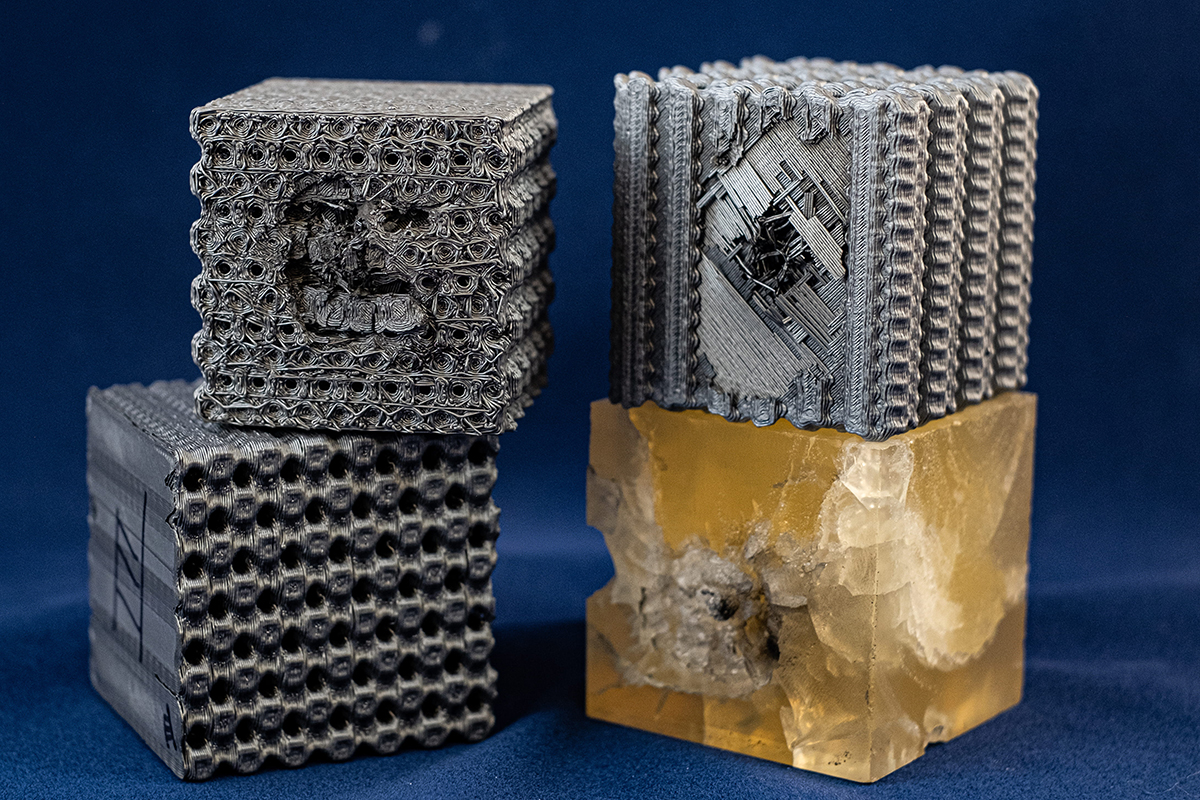 Four 3D-printed blocks, two gray stacked, the top with a dent, at right a gray block with a dent over a broken yellow block. These demonstrate the structures of Tubulanes