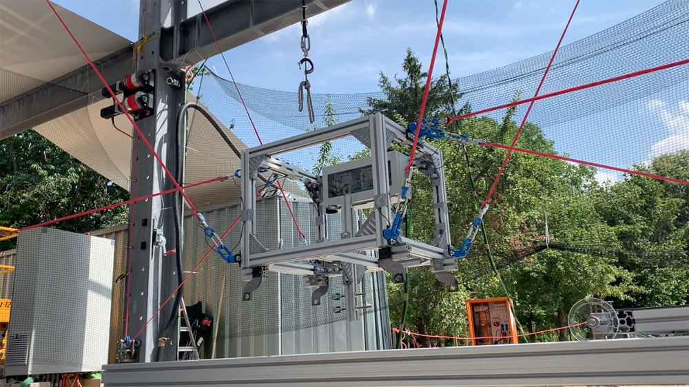 A robot in the form of a metal box is attached to various red cables and suspended a few feet in the air, unveiled for the Bauhaus centennary