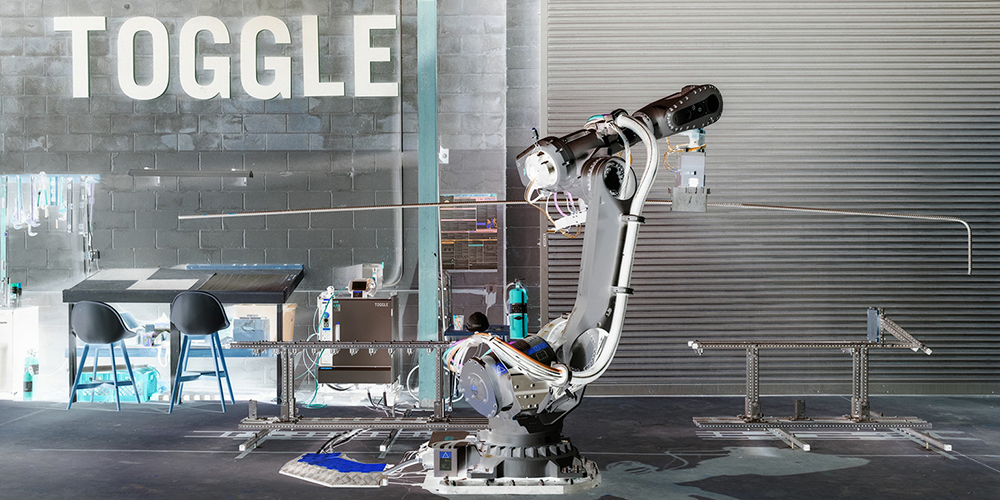 "Photo of a robot arm in front of a sign reading ""TOGGLE"""
